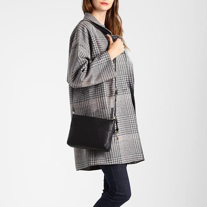 Sac bandoulière en cuir pour femme porté avec un par-dessus gris.