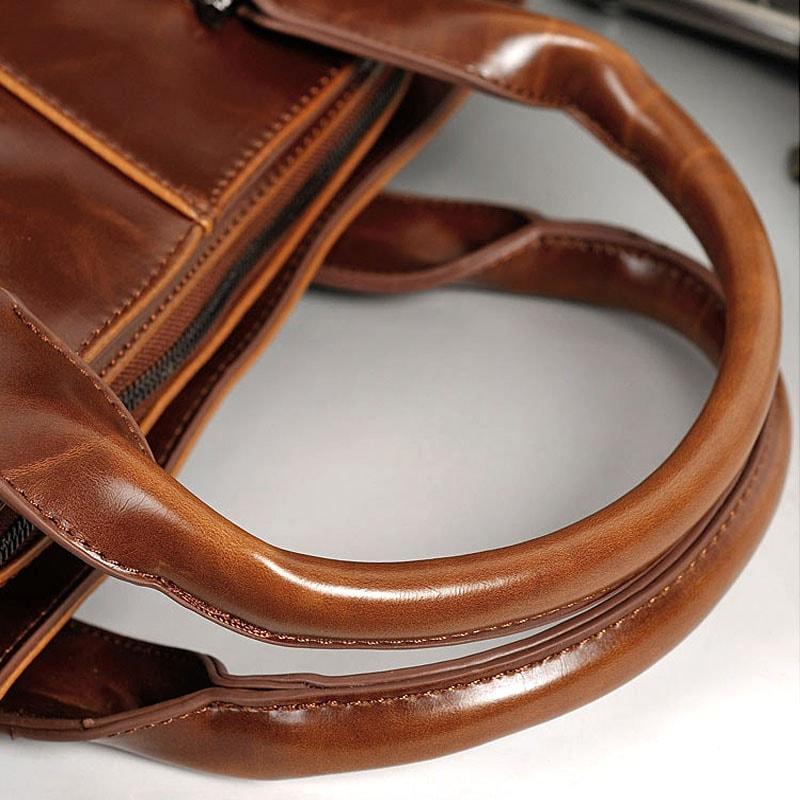 Détails des anses du sac porte-documents et ordinateur pour homme en cuir marron.