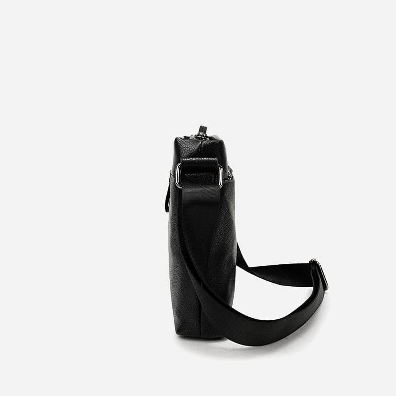 Côté de la sacoche besace pour homme en cuir noir avec sa bandoulière.