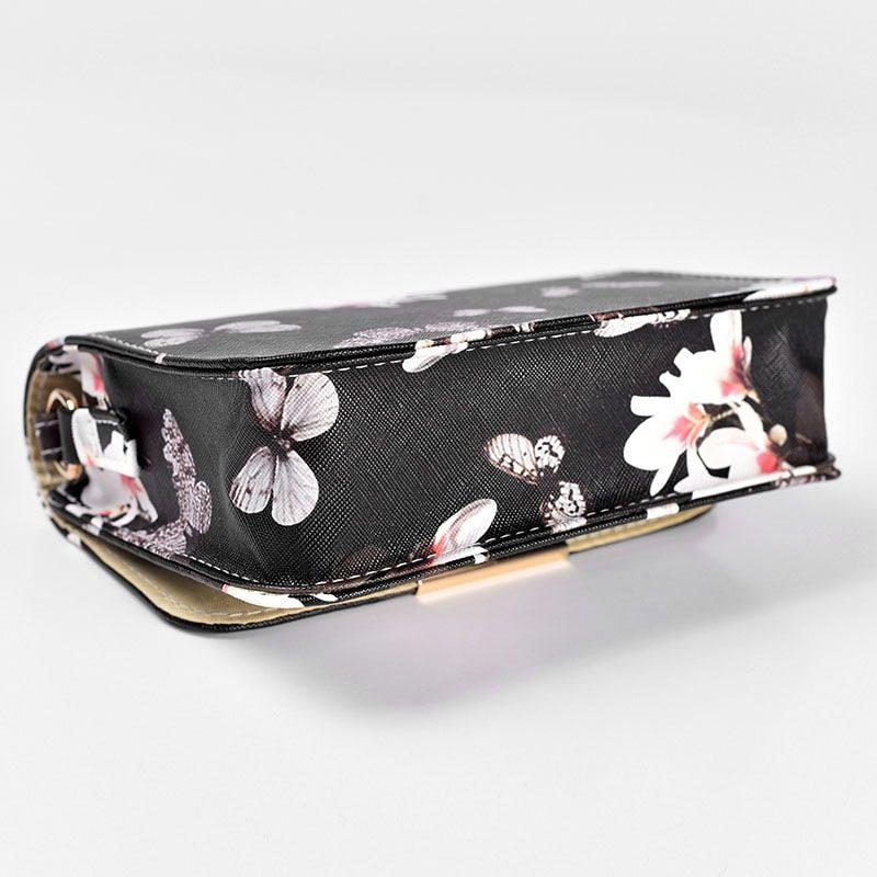 Dessous du sac besace bandoulière cuir noir avec imprimé floral et empiècement de couleur or.