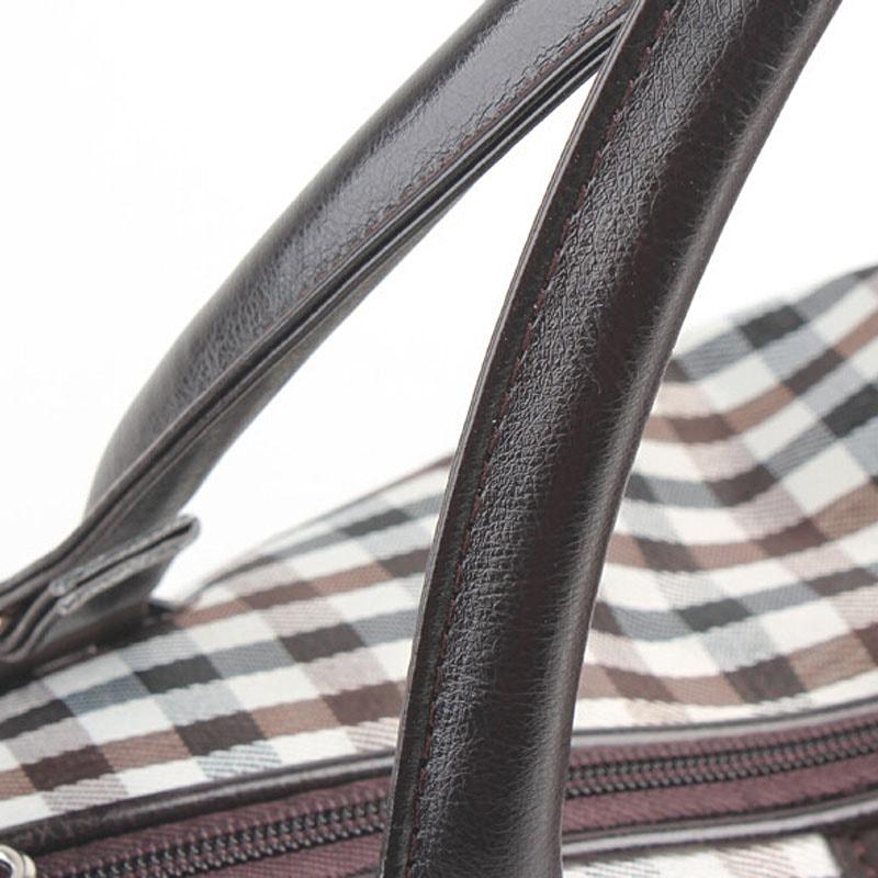 Détails des anses en cuir du sac weekend pour homme et femme en toile et en cuir avec motifs à carreaux.
