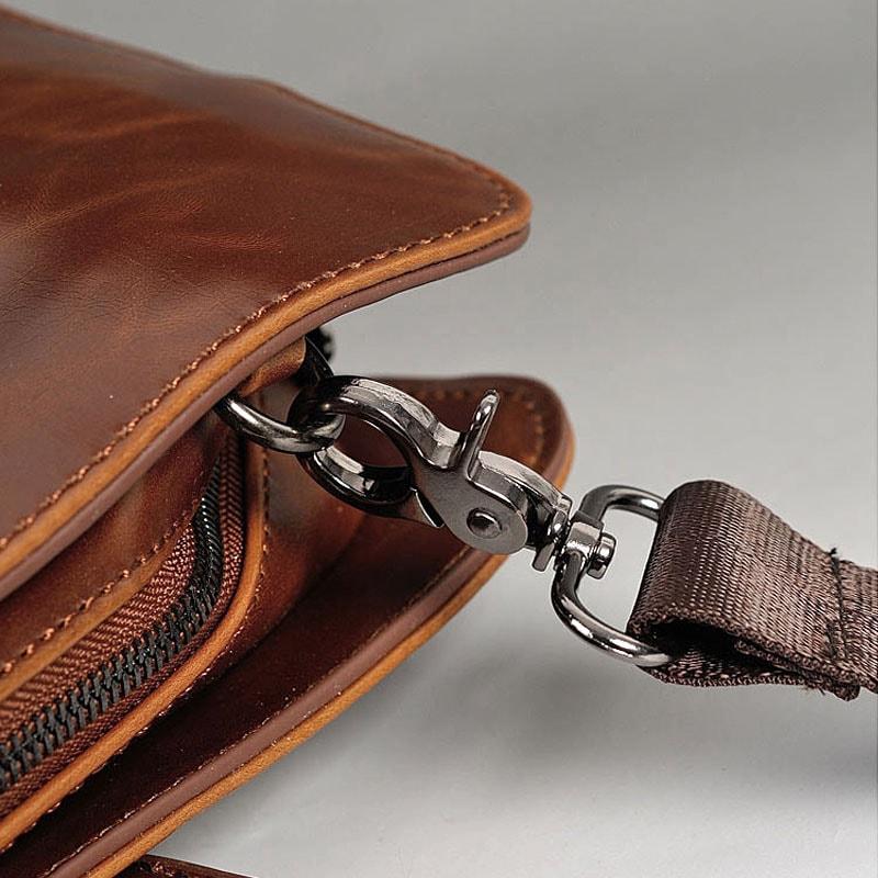 Détail encoche, empiècement métallique et bandoulière de la sacoche cuir pour homme.