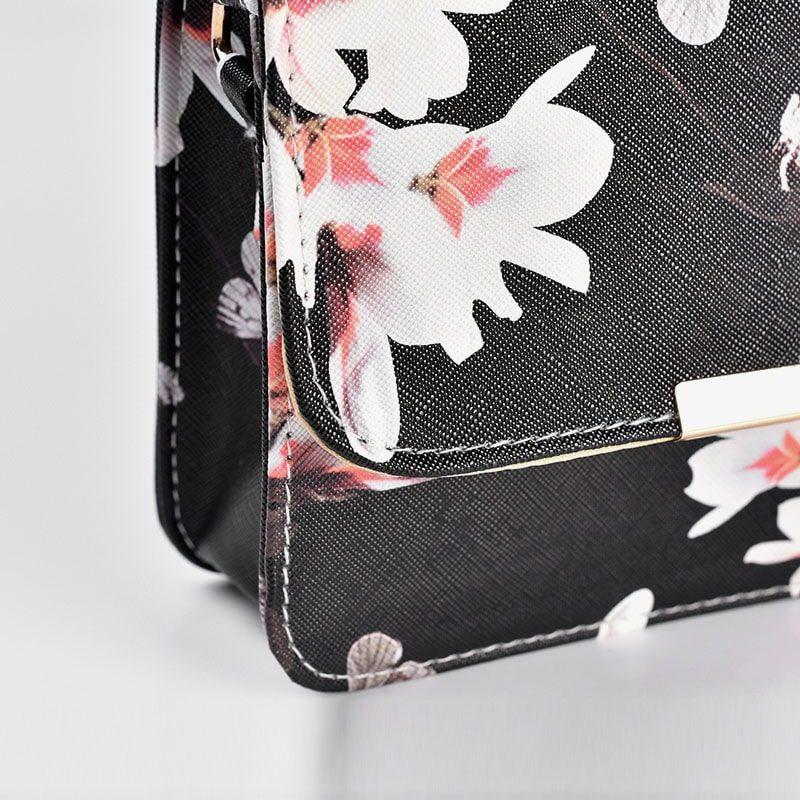 Détails du sac besace bandoulière cuir noir avec imprimé floral et empiècement de couleur or.