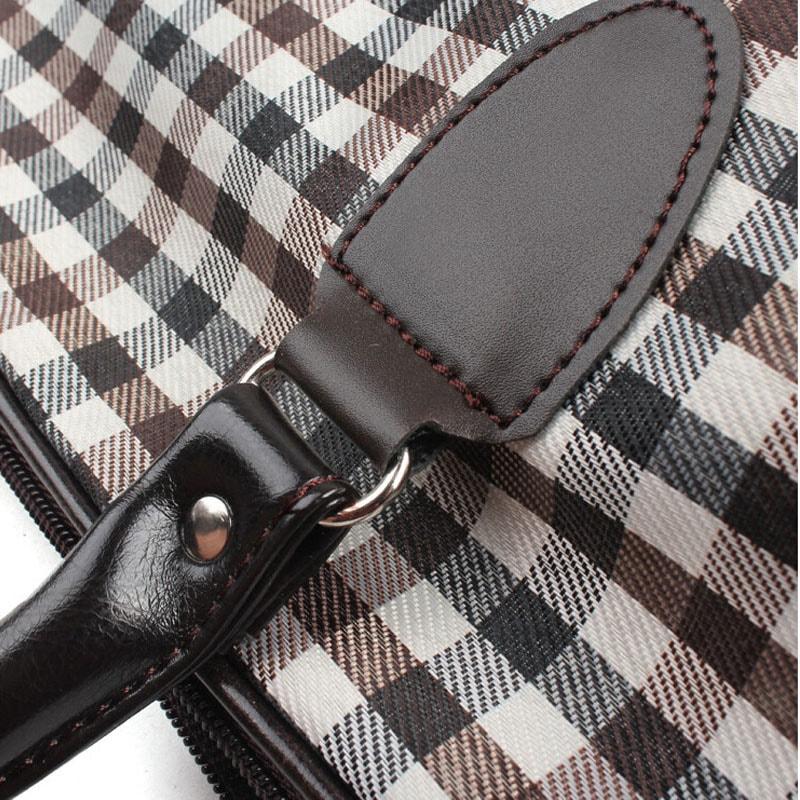 Détail encoche du sac de voyage pour homme et femme en toile et en cuir avec motifs à carreaux.