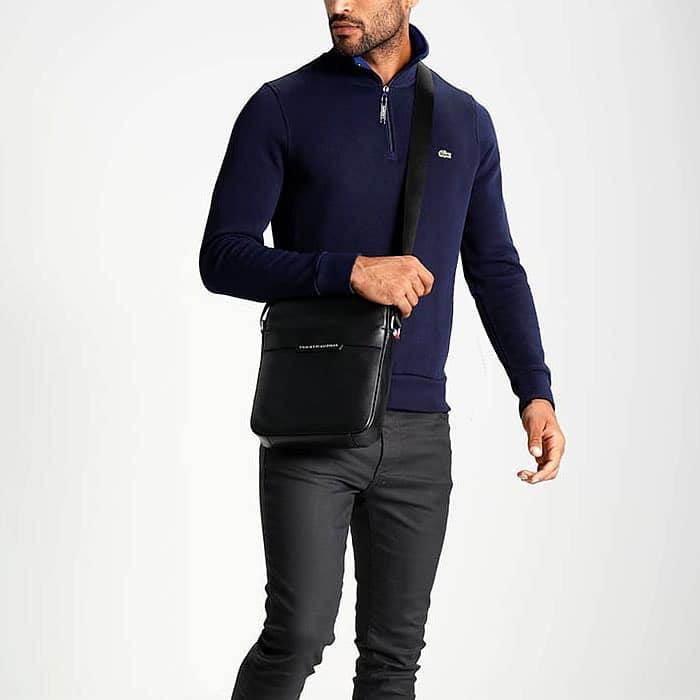 Petite sacoche pour homme en cuir noir portée en bandoulière.