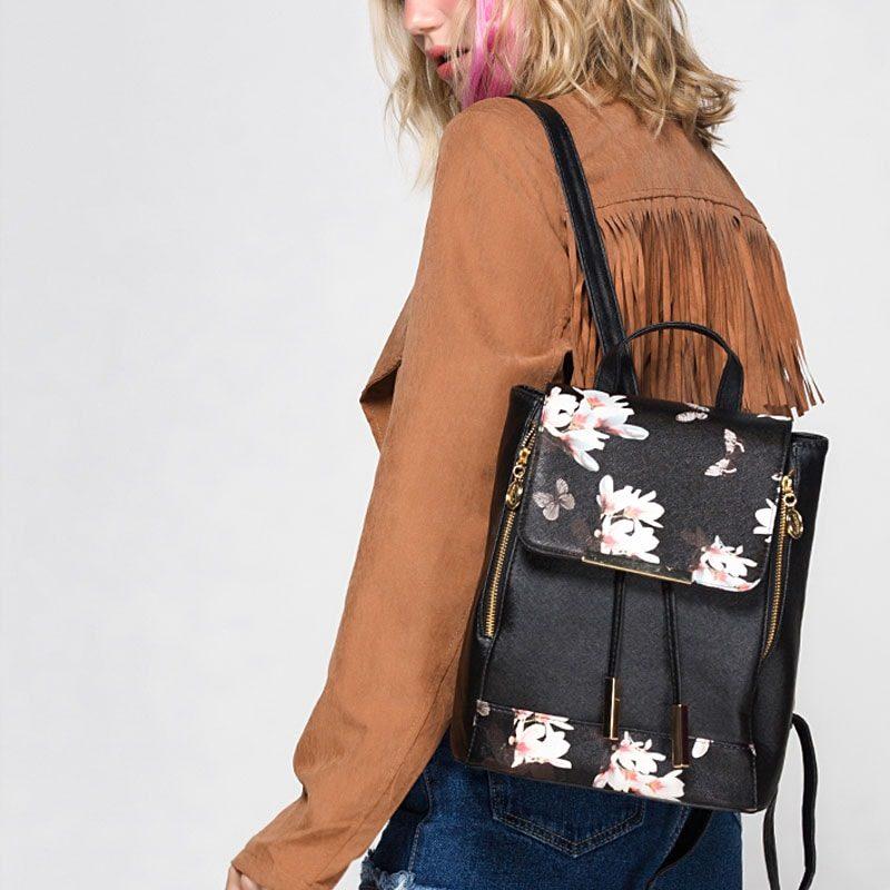 Modèle avec sac à dos cuir texturé noir avec imprimé à fleurs.