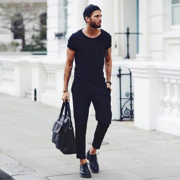 Homme qui se promène dans la rue avec son sac à main bandoulière en cuir porté à la main.