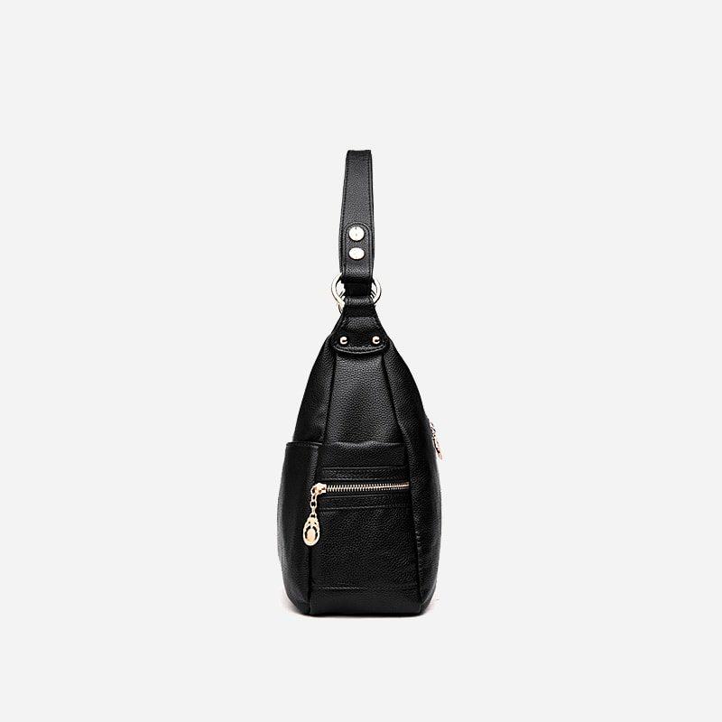 Sac bandoulière pour femme en cuir noir. 2 poches à zip sur le côté.