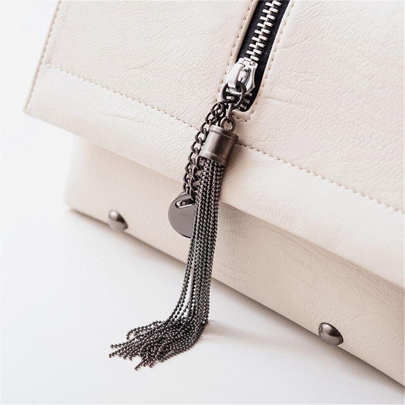 Détails du sac besace blanc pour femme avec bandoulière à chaîne et pompons.