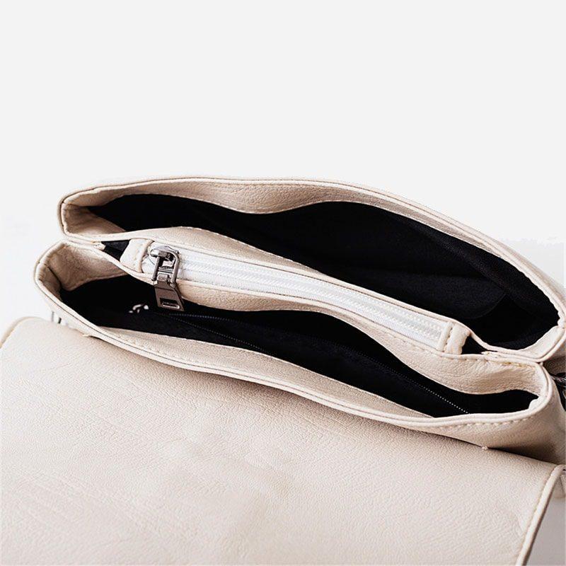 Intérieur du sac besace blanc pour femme avec bandoulière à chaîne et pompons.