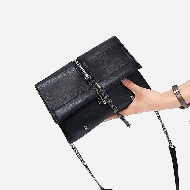 Sac besace noir pour femme avec bandoulière à chaîne et pompons. Porté main.