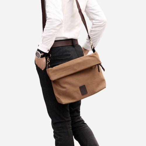 Sac besace en toile de couleur marron avec sa bandoulière brune. Sacoche avec fermeture à rabat façon plié.