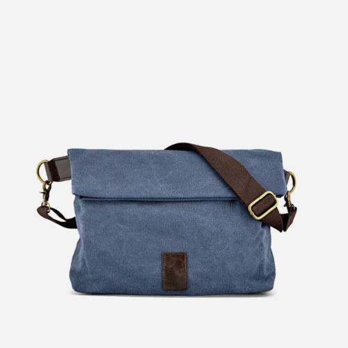 Sac besace en toile de couleur bleu avec sa bandoulière brune. Sacoche avec fermeture à rabat façon plié.