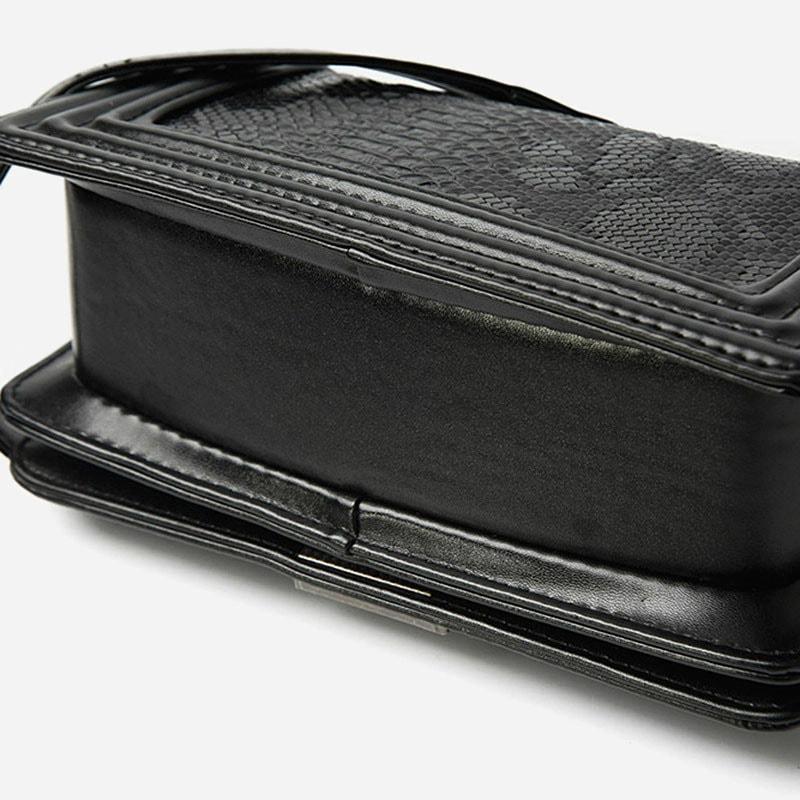 Détails du dessous du sac besace pour femme avec bandoulière à chaîne et matière en cuir croco noir.
