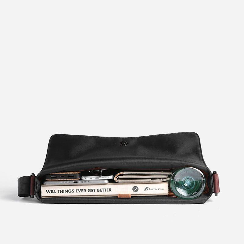 Intérieur du sac besace en toile noir avec languette en cuir marron pour homme.