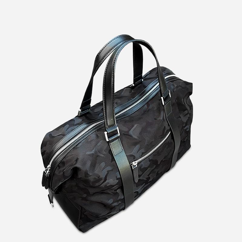 Sac de voyage noir camouflage militaire avec poche zippée au verso, 2 anses et pièces en cuir et nylon.