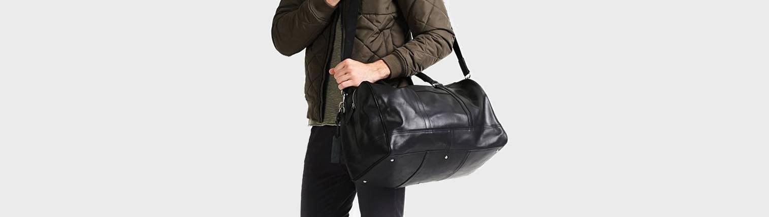 Sac de voyage en cuir noir pour homme porté en bandoulière via l'épaule.