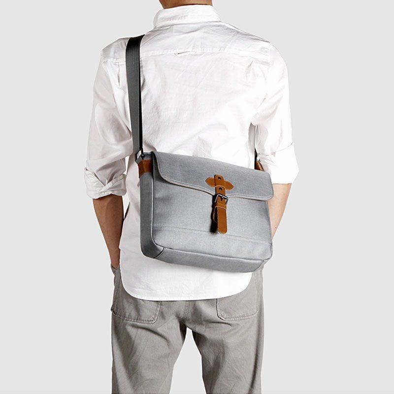 Sacoche besace en toile gris pour homme avec bandoulière amovible et pièces en cuir marron porté via l'épaule.