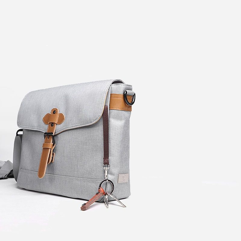 Côté de la sacoche besace en toile gris pour homme avec bandoulière amovible et pièces en cuir marron.