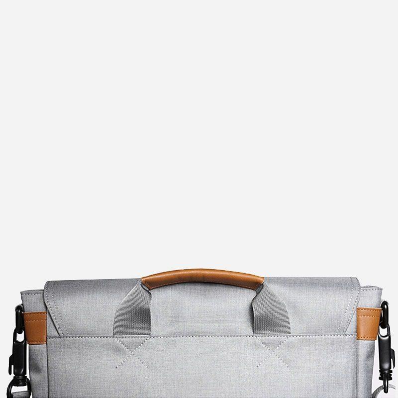 Verso de la sacoche besace en toile gris pour homme avec bandoulière amovible, pièces en cuir marron et poignée.