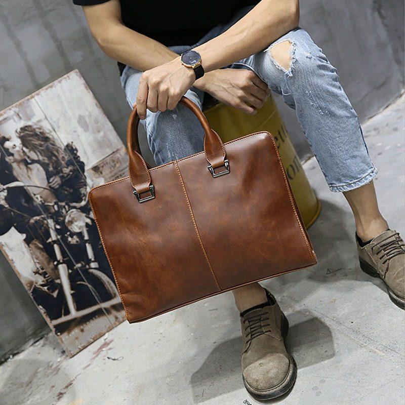 Sac porte-documents et ordinateur pour homme dans sa version en cuir marron et porté main.