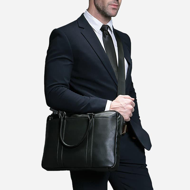 Sac à bandoulière et sac à main en cuir noir pour homme avec plusieurs poches zippées et poches intérieures. Vormbag Famous. Mannequin homme avec sac bandoulière.