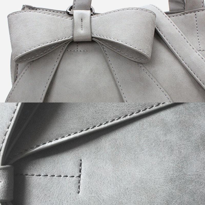 Sac à main bandoulière cuir pour femme de couleur gris avec nœud papillon. Détails.