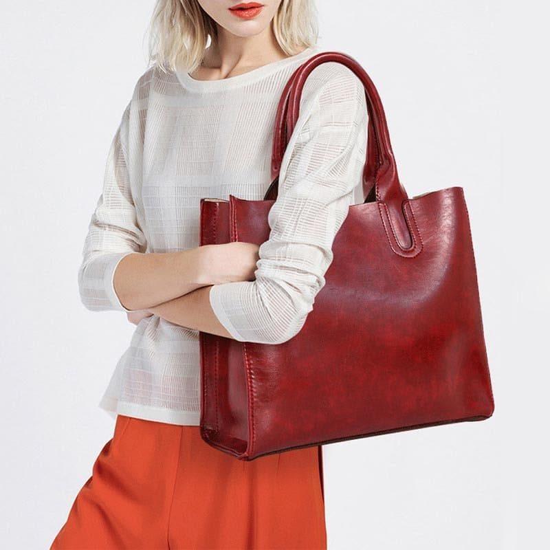 Sac à main cuir rouge pour femme porté via épaule comme une bandoulière.