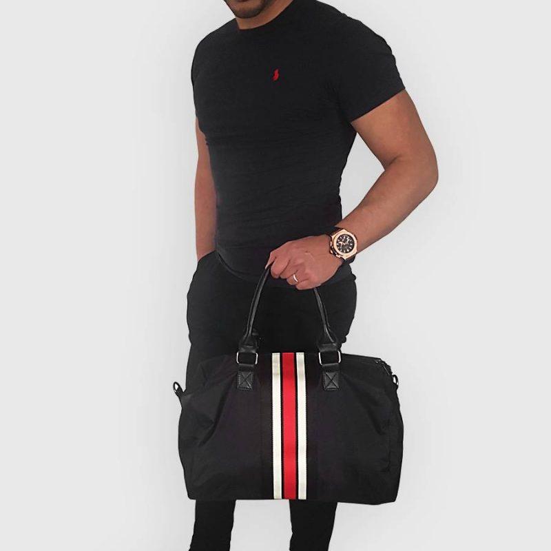 Sac weekend 48h pour homme portée main de couleur noir avec bandes rouges et blanches.