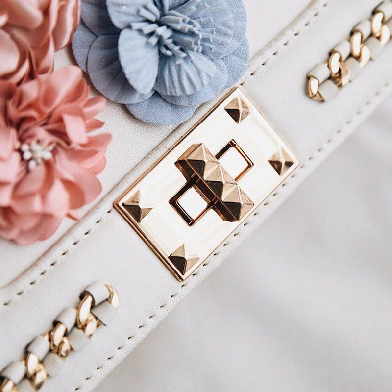 Sac à main pour femme en cuir blanc avec fleurs et bandoulière à chaîne. Zoom.