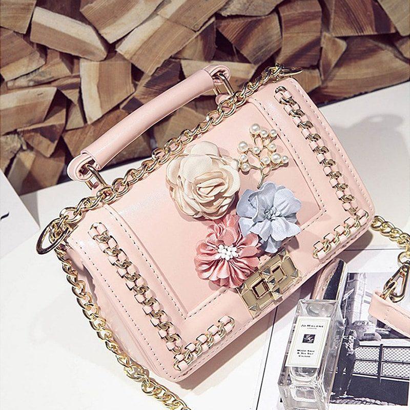 Sac à main pour femme en cuir rose avec fleurs et bandoulière à chaîne.