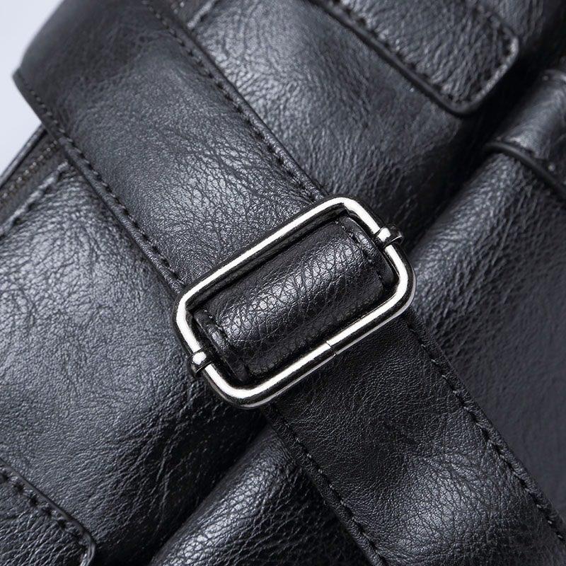 Sacoche pour homme en cuir noir avec bandoulière, rabat et poignée pour être portée comme sac à main. Détails.