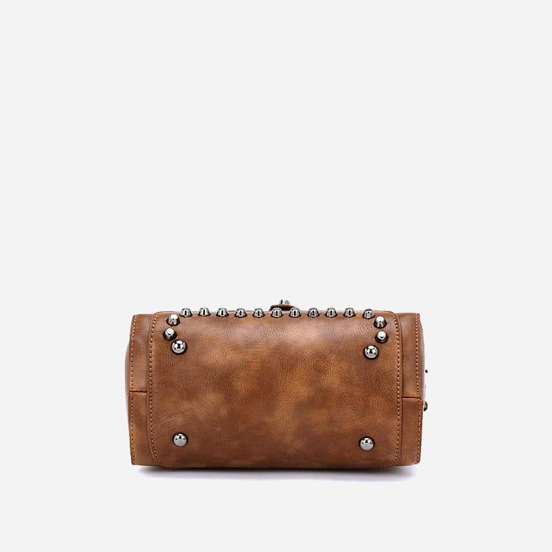 Dessous du sac à main clouté en cuir marron pour femme avec bandoulière et languette.