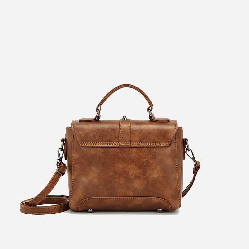 Verso du sac à main clouté en cuir marron pour femme avec bandoulière et languette.