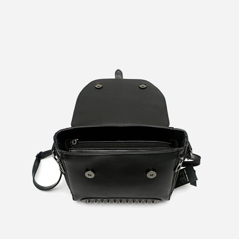 Détails du sac à main clouté en cuir noir pour femme avec bandoulière et languette.