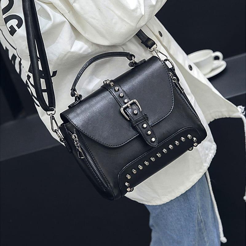 Porter épaule du sac à main clouté en cuir noir pour femme avec bandoulière et languette.