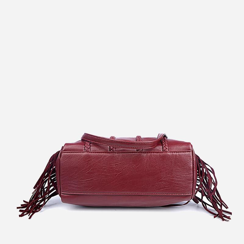 Dessous du sac à main bandoulière en cuir rouge clouté et frangé.