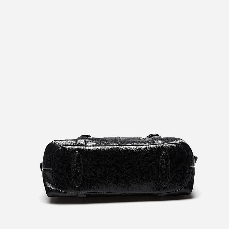 Dessous du sac cabas en cuir noir pour femme avec bandoulière, languettes et fermeture décorative.