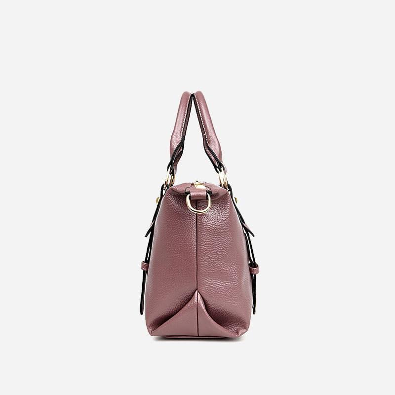Côté du sac cabas en cuir rose pour femme avec bandoulière, languettes et fermeture décorative.