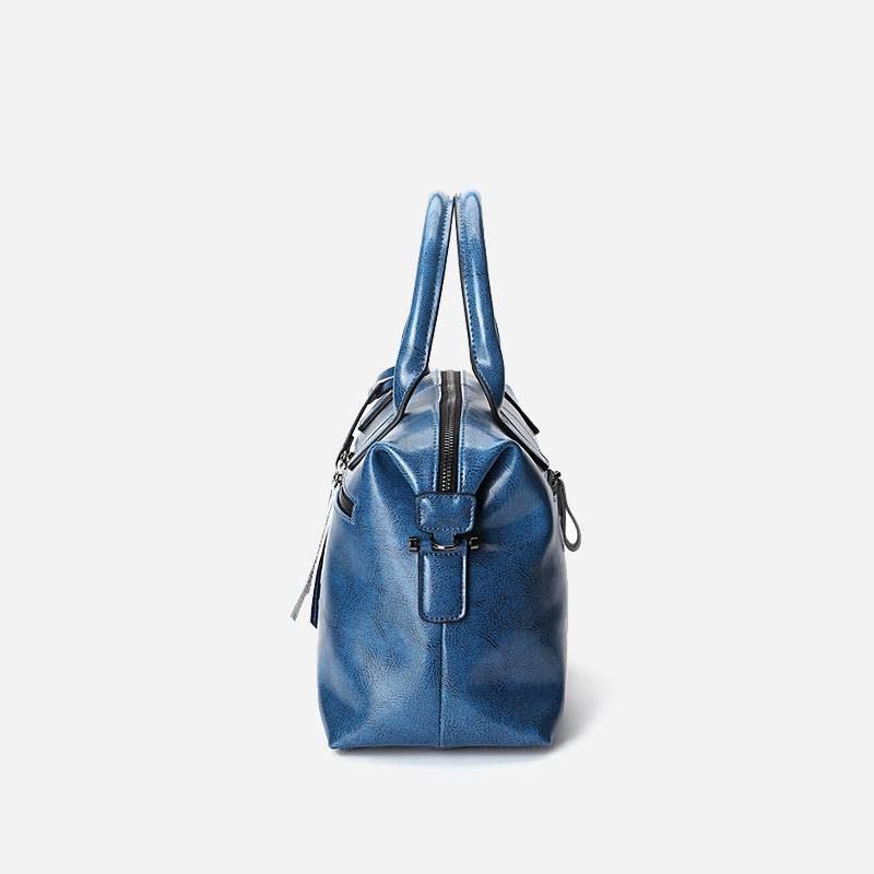 Côté du sac à main bandoulière pour femme en cuir véritable de couleur bleu.