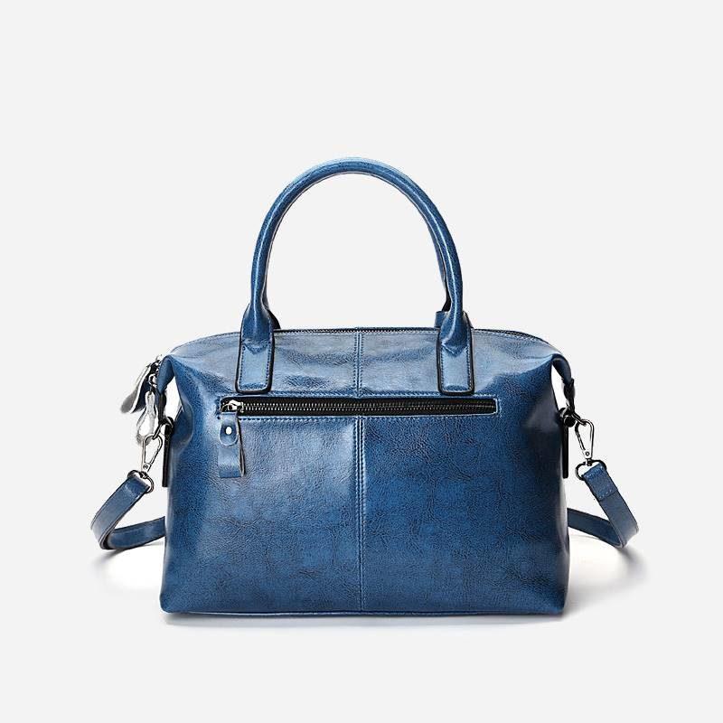 Verso du sac à main bandoulière pour femme en cuir véritable de couleur bleu.