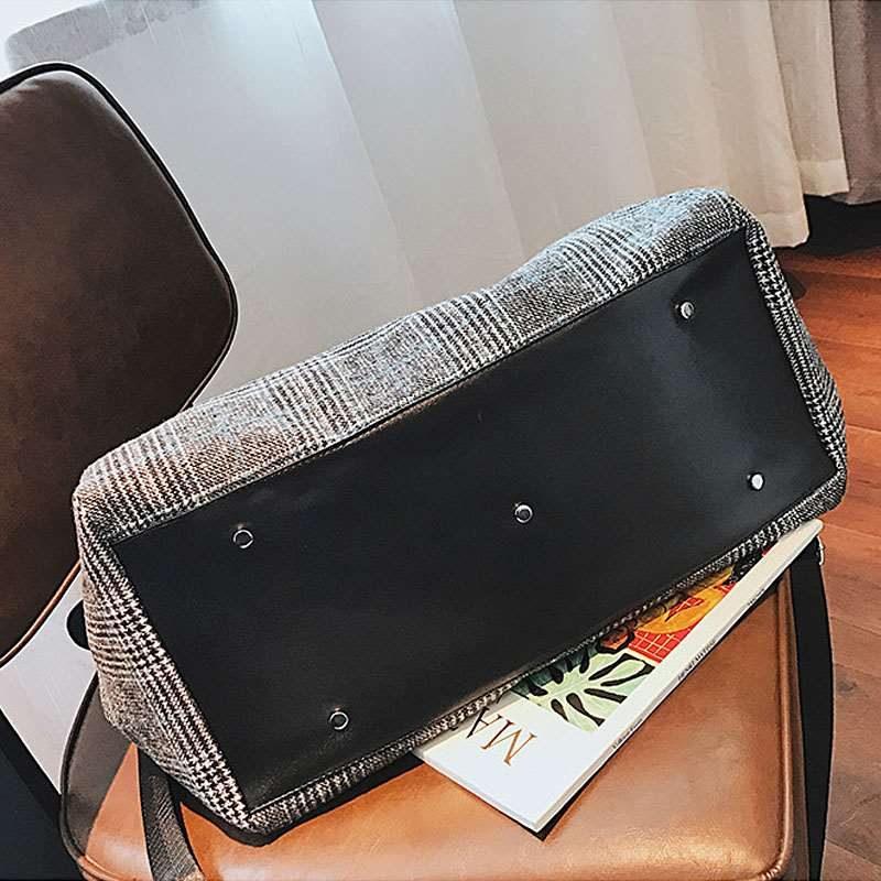 Dessous du sac de voyage gris en toile avec motifs pour femme.