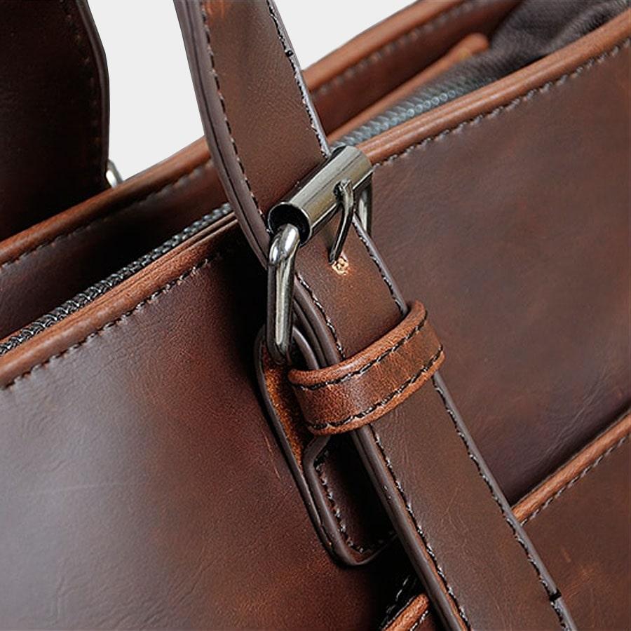 Détails de la boucle de ceinture du sac porte-document en cuir brun.