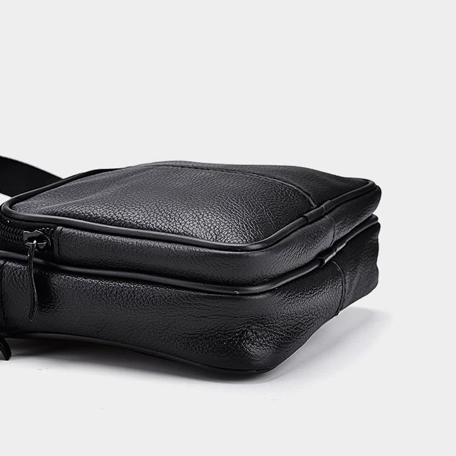 Dessous du petit sac trotteur homme en cuir noir véritable avec poche à zip.
