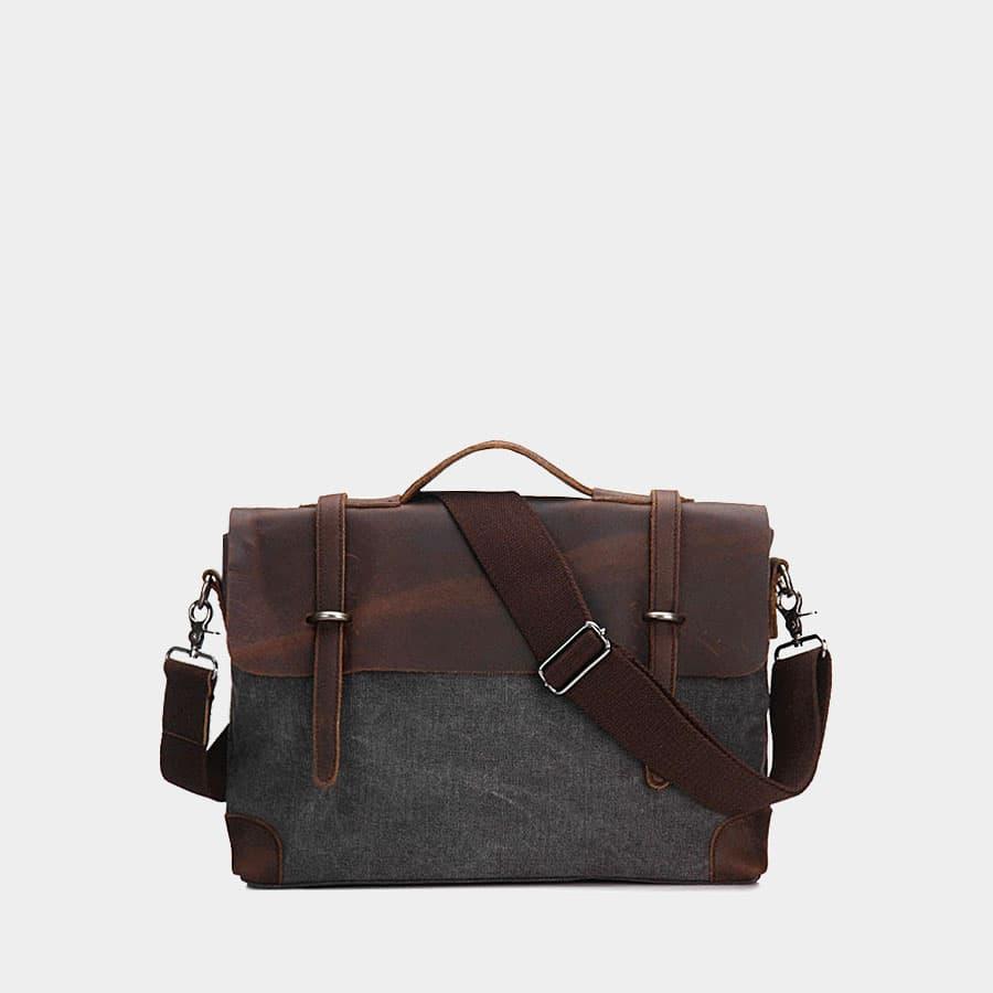 Sacoche besace bi-ton en toile noire et cuir véritable brun foncé.