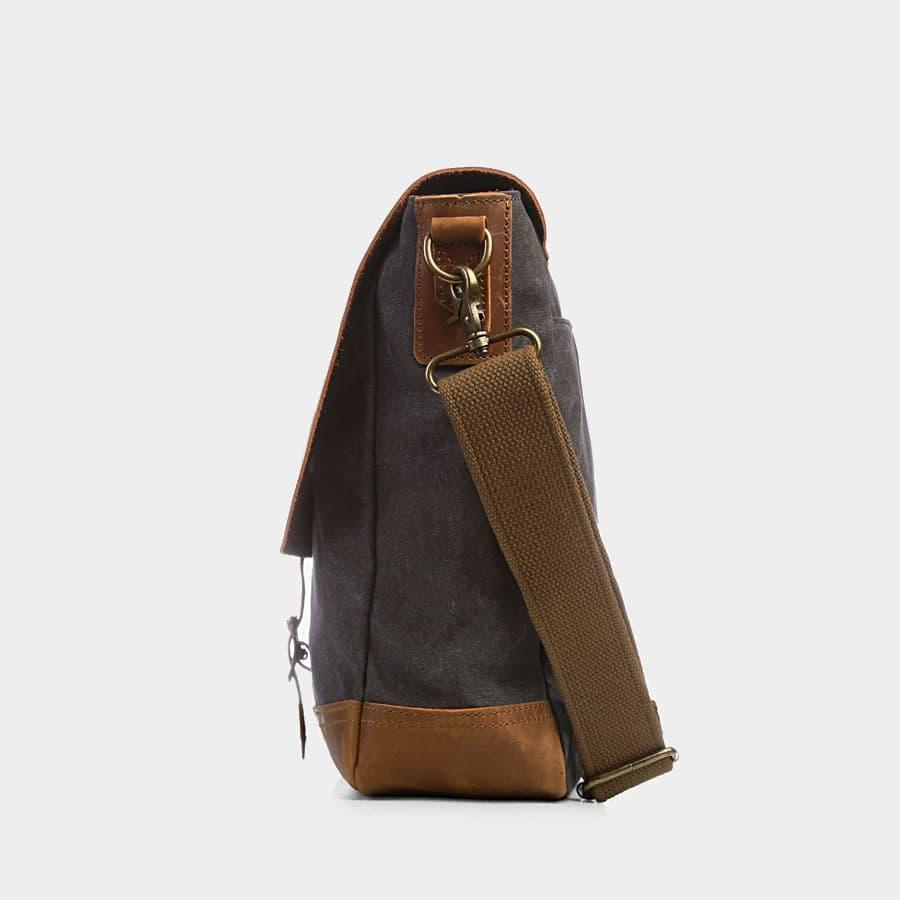 Côté de la sacoche façon besace en toile bleu et cuir véritable marron.