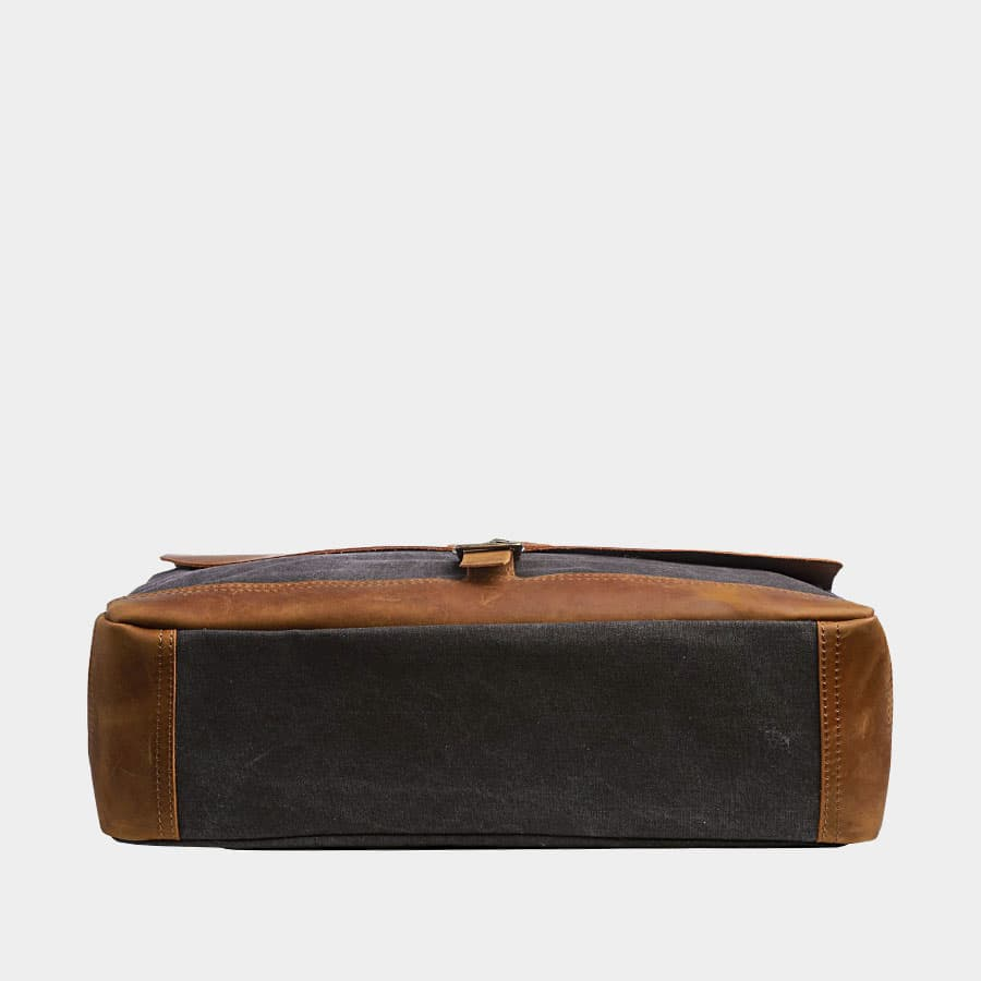 Dessous de la sacoche façon besace en toile bleu et cuir véritable marron.