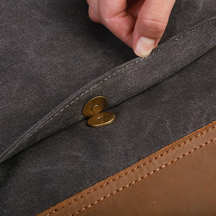 Détail du bouton poussoir aimanté, des coutures sur toile et cuir.