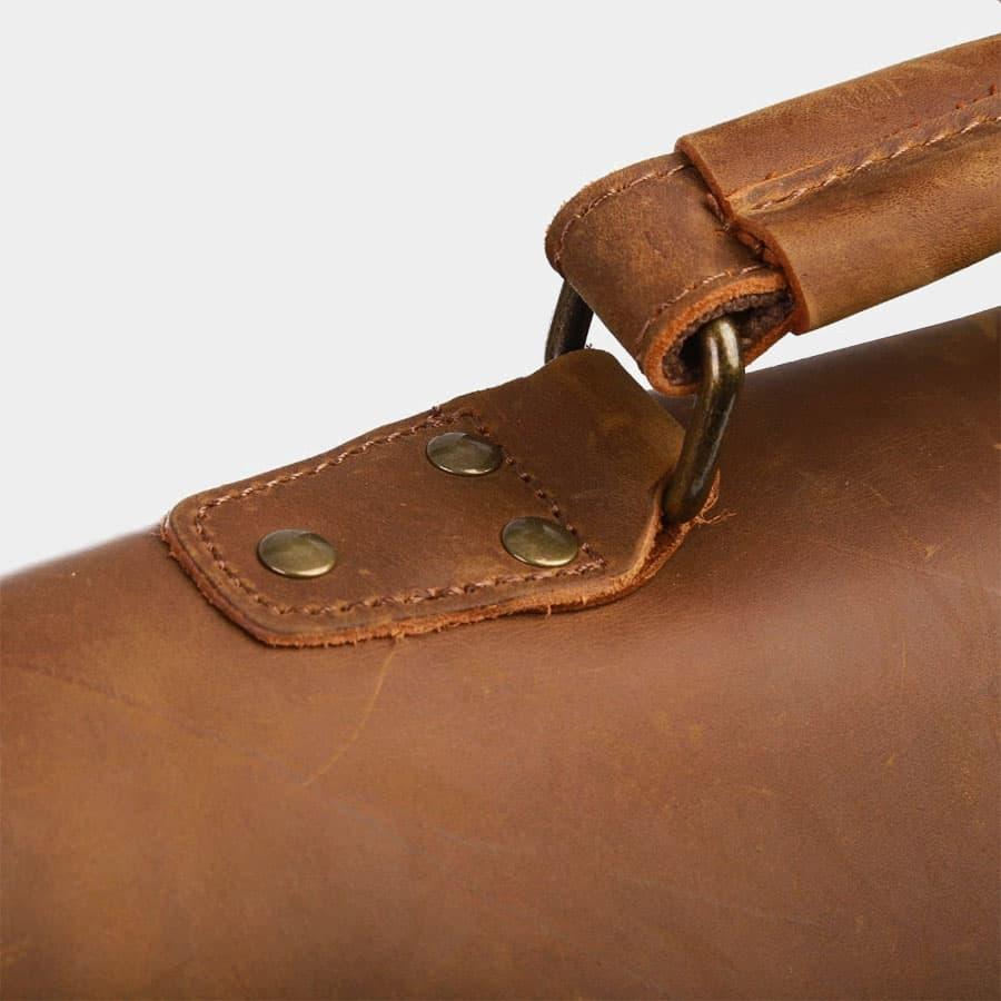 Détails de l'anse du sac avec les rivets de renfort et le cuir épais.