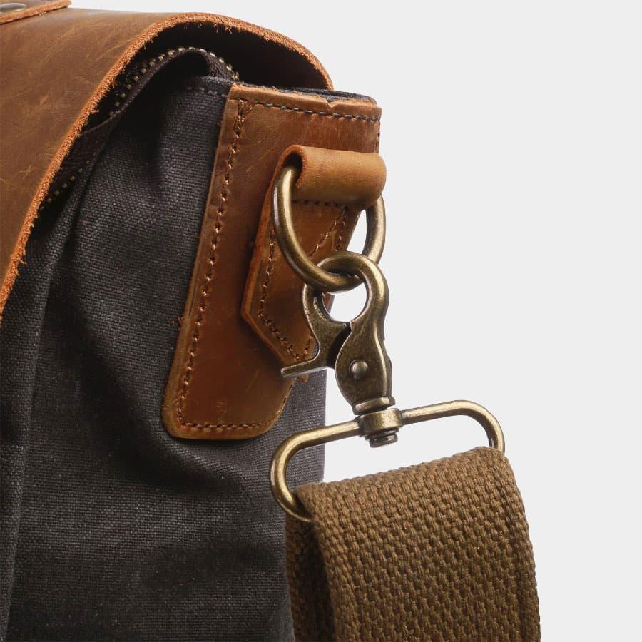Détails du mousqueton métallique couleur bronze, de la bandoulière et de l'encoche cuir.